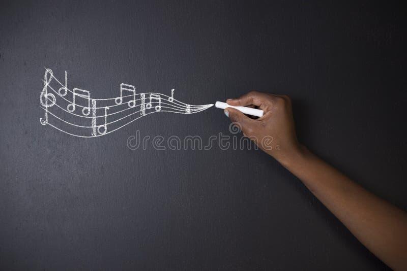 Südafrikanische oder Afroamerikanerlehrer oder -student lernen Sie Musik die mit Kreidehintergrund stockfotografie