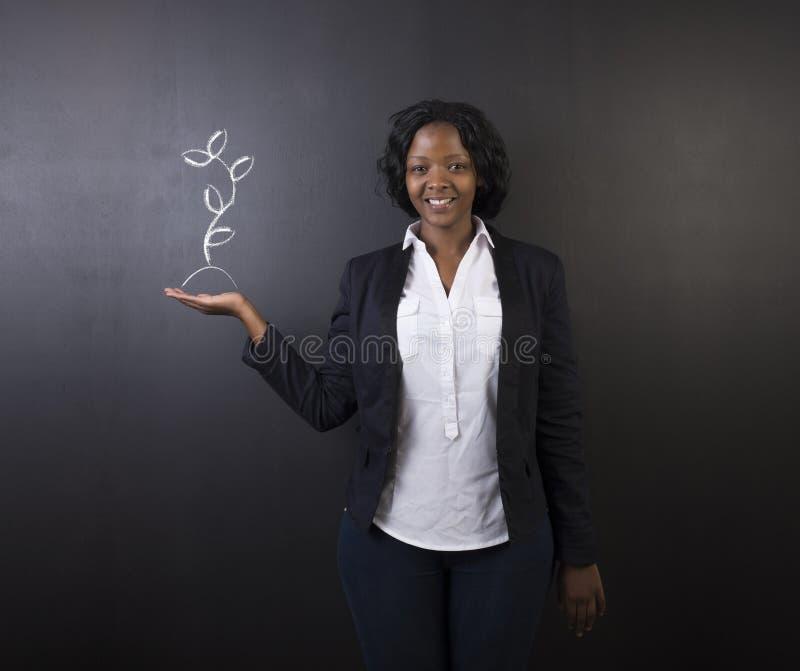 Südafrikanische oder Afroamerikanerlehrerin oder -student gegen die Tafel, die Kreide growng Anlage hält stockbild