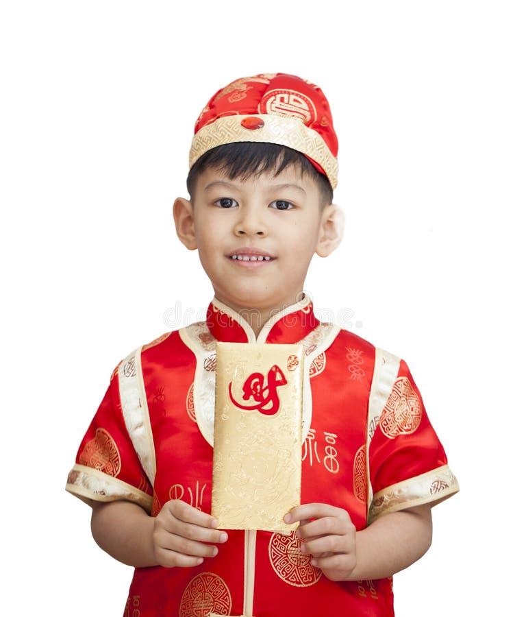 Südostasiatischer entzückender Junge im cheongsam übergibt das Halten des roten Satzes lizenzfreie stockfotografie
