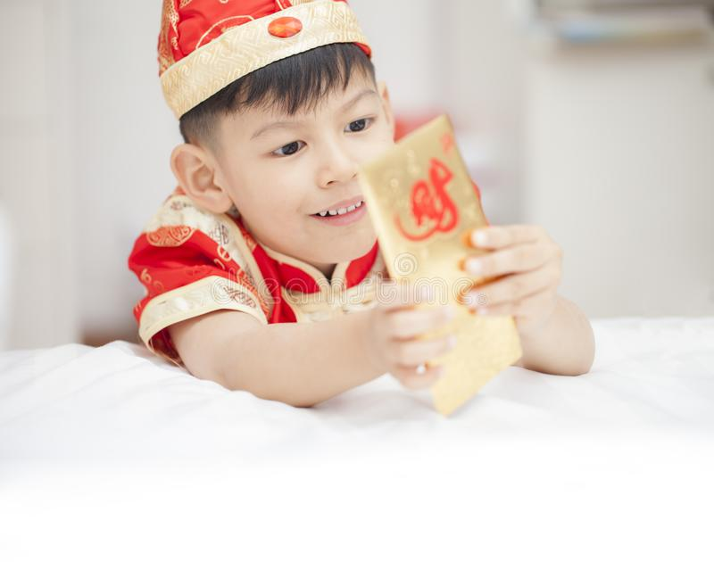 Südostasiatischer entzückender Junge im cheongsam übergibt das Halten des roten Satzes stockbild