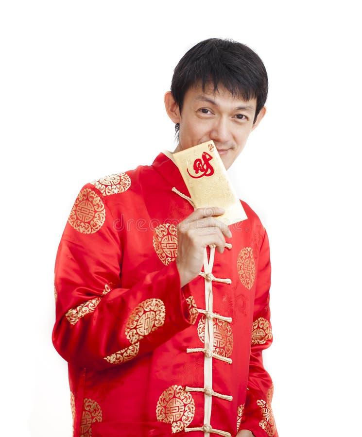 Südostasiatischer Mann in cheongsam Händen, die rote Pakete, ANG-Kriegsgefangen, lokalisiert auf weißem Hintergrund halten stockfoto