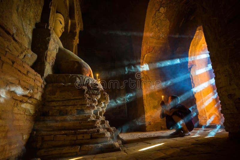 Südostasiatischer Neophyt, der mit Kerzenlicht in einem Buddihist-Tempel betet stockfoto