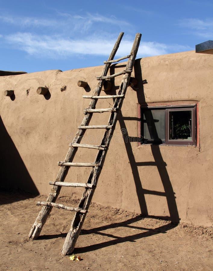 Südwestliche Leiter, die an der Lehmziegelmauer in Taos-Pueblo sich lehnt stockfotografie