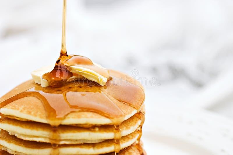 Süssen Sie das Schütten auf Pfannkuchen mit Sirup lizenzfreies stockfoto