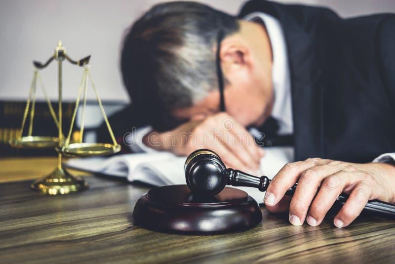 Sądzi młoteczek z prawnikami, młoteczek na drewnianym stole i prawniku doradcy lub samiec jest zmęczonych i migreny migrenami pod zdjęcia stock