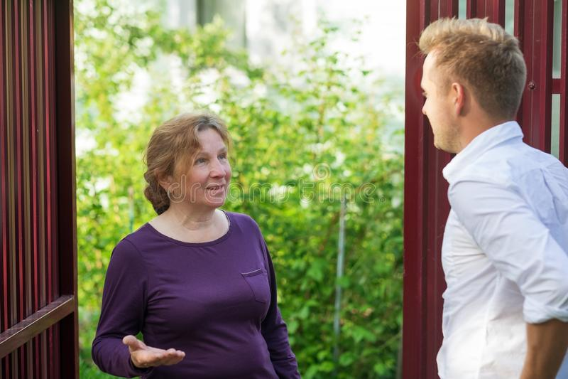 Sąsiad dyskutują wiadomość, stoi przy ogrodzeniem Starsza kobieta opowiada z młodym człowiekiem obraz royalty free
