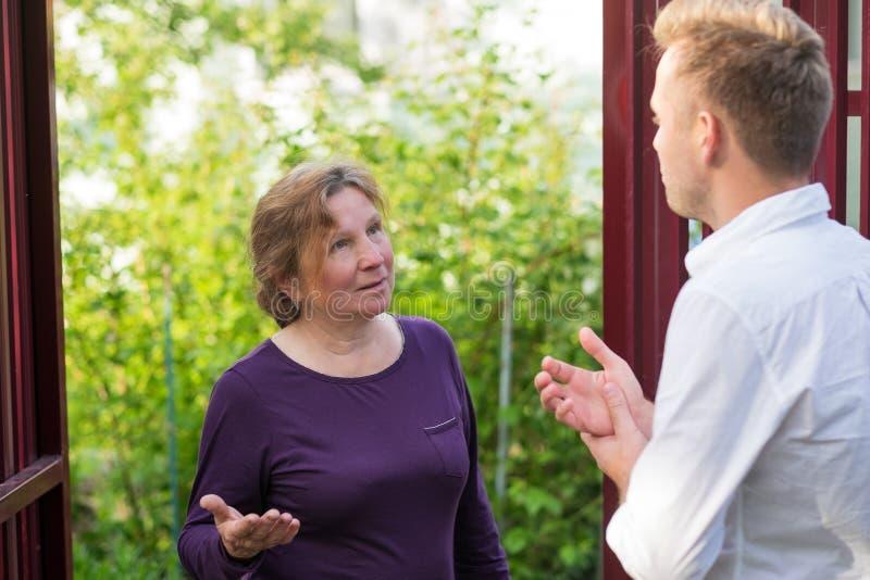 Sąsiad dyskutują wiadomość, stoi przy ogrodzeniem Starsza kobieta opowiada z młodym człowiekiem fotografia royalty free