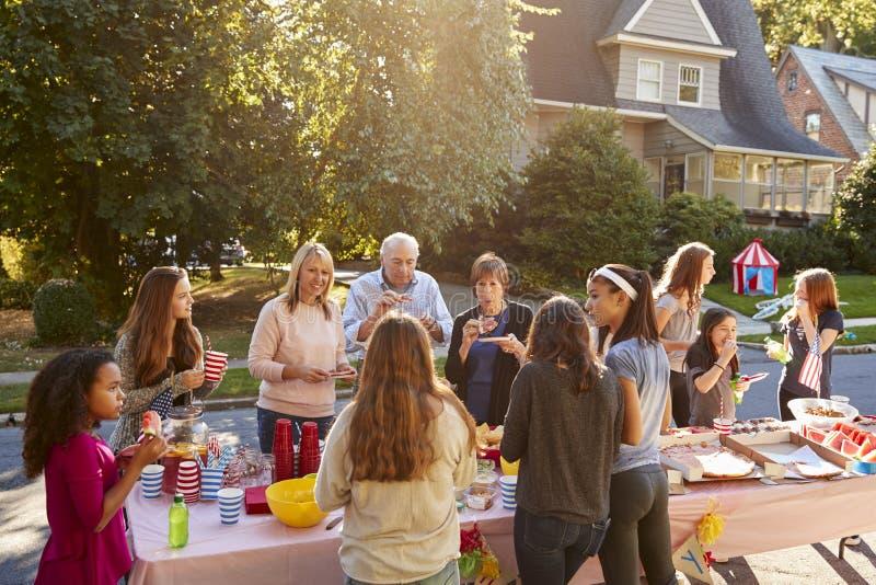 Sąsiad opowiadają i jedzą wokoło stołu przy blokowym przyjęciem fotografia stock