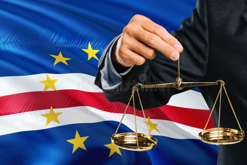Sędzia trzyma złote skale sprawiedliwość z przylądka Verde falowania flagi tłem Równość temat i legalny pojęcie obrazy royalty free