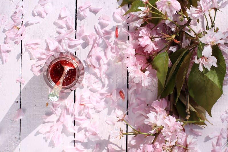 Słój świeży malinowy dżem na lekkim wieśniaka stole zakrywającym z wiśnią kwitnie, romantyczny śniadaniowy tło, zamyka up, w dzią obraz royalty free