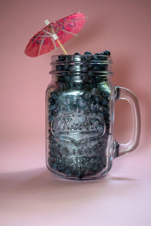 Słój czarne jagody na różowym tle 3 obraz stock