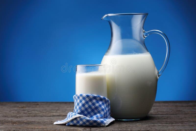 Słój i szkło z niektóre mlekiem na błękicie obraz royalty free