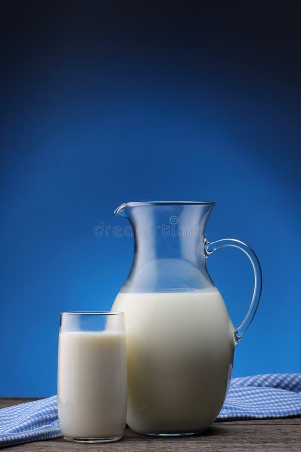 Słój i szkło z niektóre mlekiem na błękicie zdjęcie stock