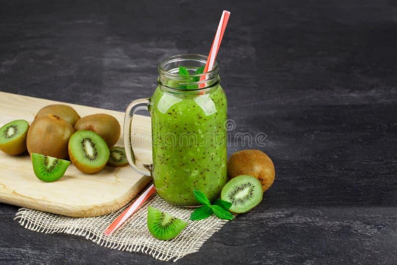 Słój kiwi sok na czarnym stołowym tle Świeże kiwi owoc na tnącym biurku Zdrowy zielony sok kosmos kopii zdjęcie stock