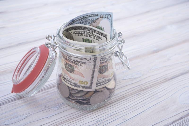 Słój monety w oszczędzanie pieniądze pudełku z drzewnym białym tłem obraz stock