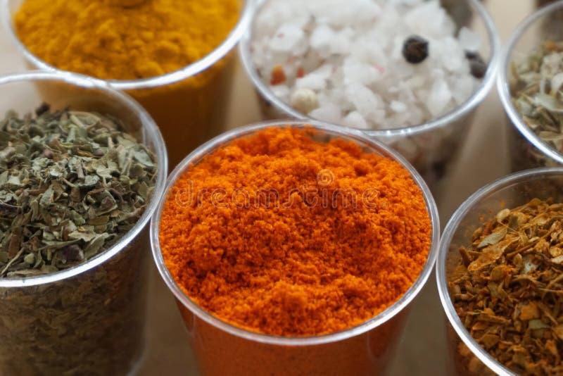 Słój pełno gorący chili pieprzy proszek w przodzie i inne pikantność w tle obrazy stock