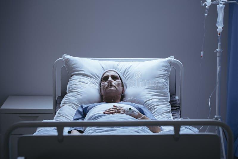 Słaba i osamotniona kobieta z nowotworem podczas chemoterapii w hos zdjęcia stock