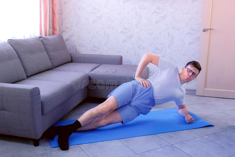 Słaby śmieszny głupka mężczyzna robi dynamicznej bocznej desce z wysiłkami na macie w domu zdjęcie stock