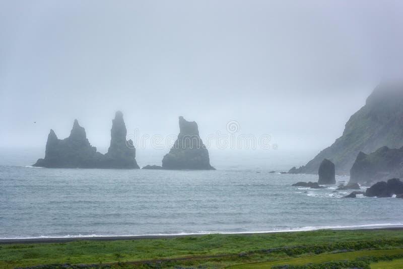 Sławne Reynisdrangar rockowe formacje, błyszczka dotykają przy czarną piaska Reynisfjara plażą, mgłowy krajobraz, Iceland fotografia stock