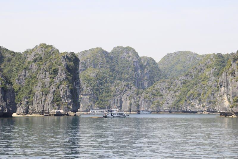 Sławni UNESCO dziedzictwa miejsca brzęczenia Tęsk zatoka z galanteryjnymi skałami, turkus wodą i łodziami, zdjęcia royalty free