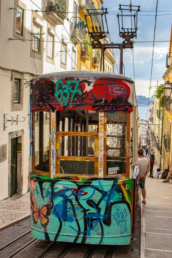 Sławny wzgórze tramwaj z graffiti w Lisbon, Portugalia Elektryczny winda pociąg Portugalczyka przewieziony pojęcie Ruch drogowy p fotografia royalty free