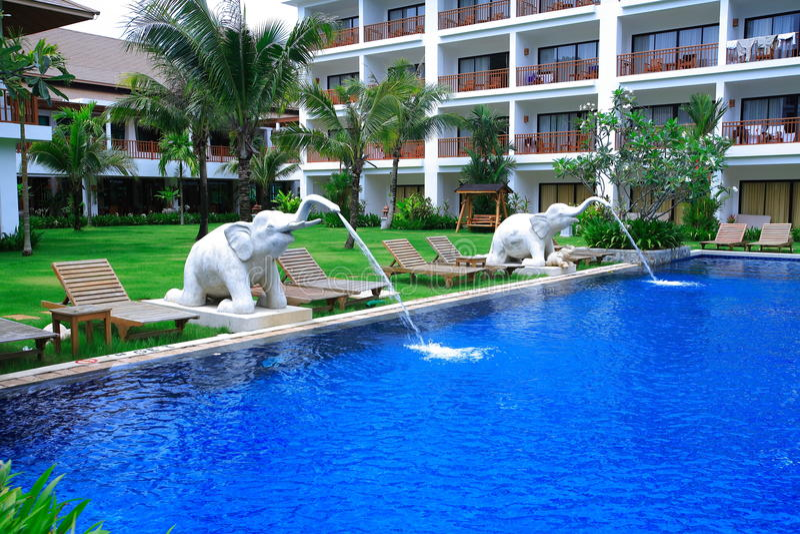 Słoń fontanny przy pływackim basenem, słońc loungers obok ogródu i budynkami, fotografia royalty free