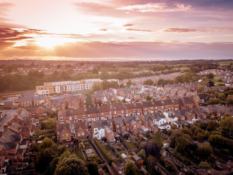 Słońca położenie z atmosferycznym skutkiem nad tradycyjnymi Brytyjski domami i drzewem wykładał ulicy fotografia royalty free