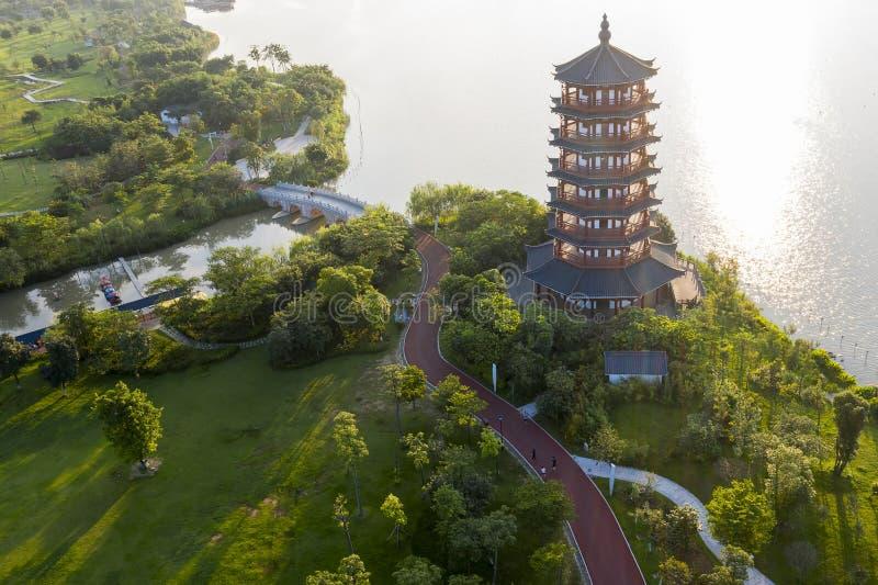 Słońce świeci na starożytnej pagodzie obok jeziora parkowego fotografia stock