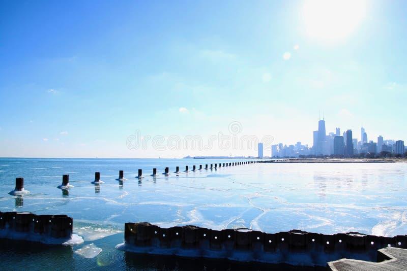 Słońce błyszczy jaskrawego nad Chicagowską linią horyzontu i zamarzniętym jezioro michigan w zimie zdjęcia royalty free
