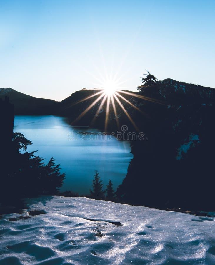 Słońce gwiazda ono pokazuje nad halnymi ` s krawędziami Krater jezioro fotografia stock