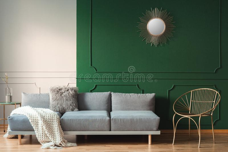 słońce kształt jak lustro na zieleni ścianie żywy izbowy wnętrze z scandinavian kanapą z poduszkami obraz royalty free