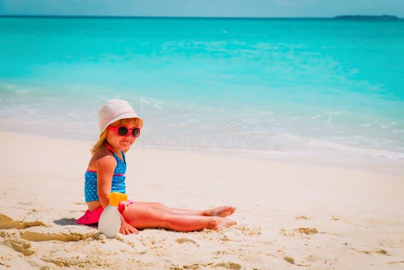 Słońce ochrona - mała dziewczynka z suncream przy plażą zdjęcia royalty free