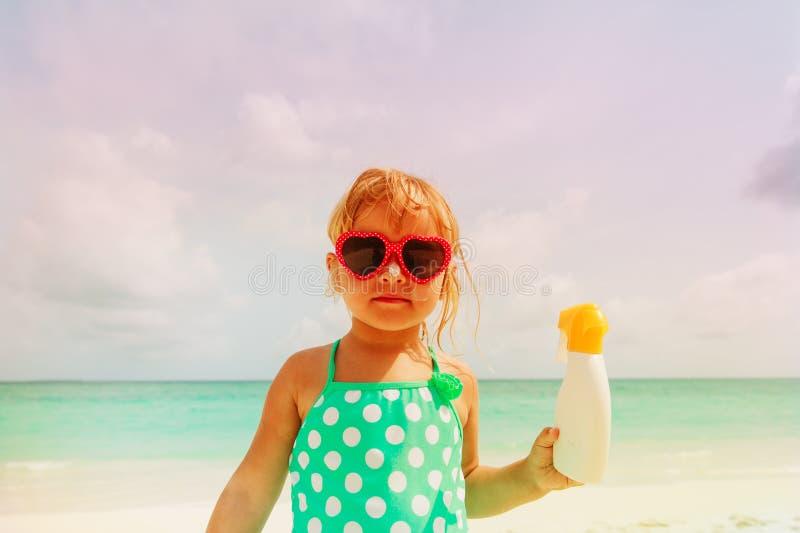 Słońce ochrony pojęcie - mała dziewczynka z suncream przy plażą zdjęcie stock