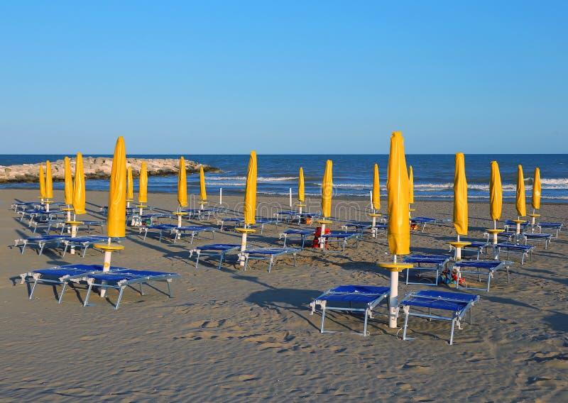 Słońce parasole na morzu wyrzucać na brzeg z słońc deckchairs i loungers fotografia royalty free