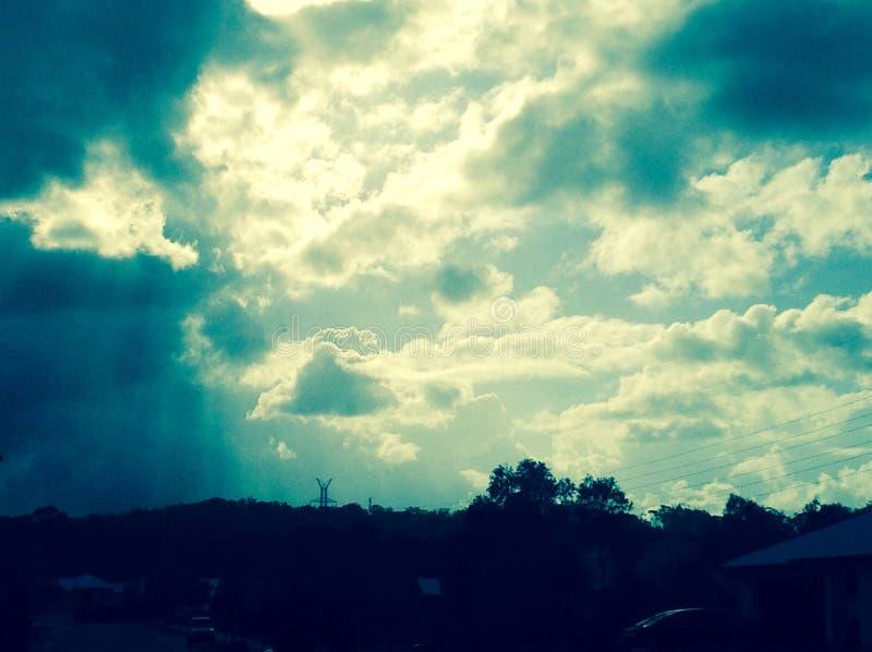 Słońce promienie błyszczy przez Ciemnych chmur zdjęcia royalty free