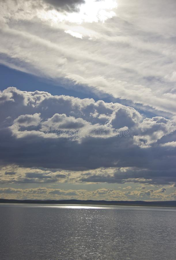 Słońce promienie robią ich sposobowi przez chmur i iluminują jezioro fotografia stock