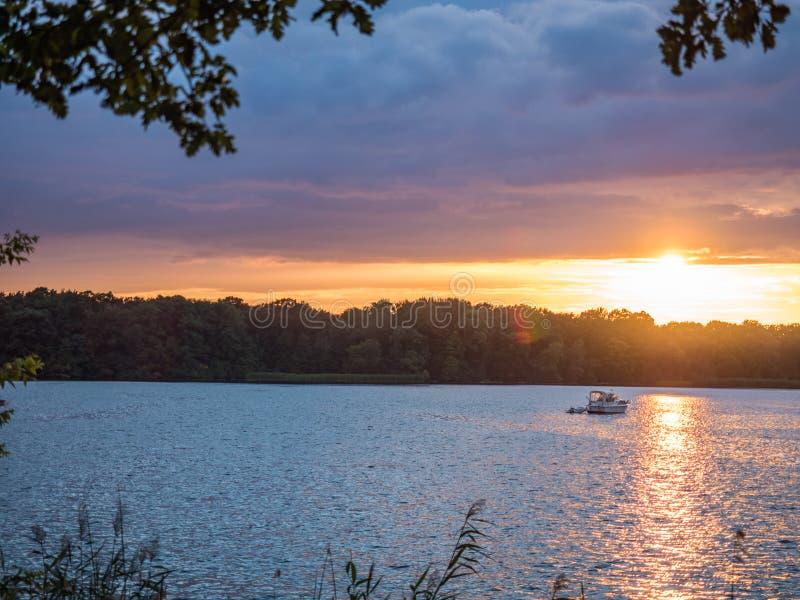 Słońce ustawia nad jeziorem w drewnach w lecie, fotografia royalty free