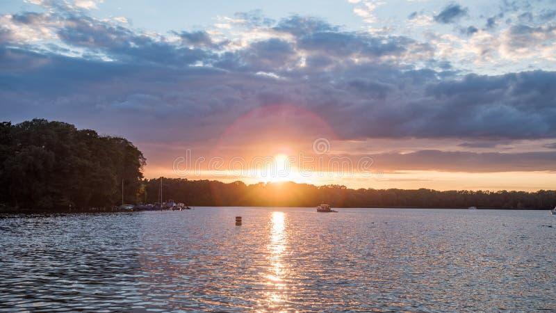Słońce ustawia nad jeziorem w drewnach w lecie, zdjęcia stock