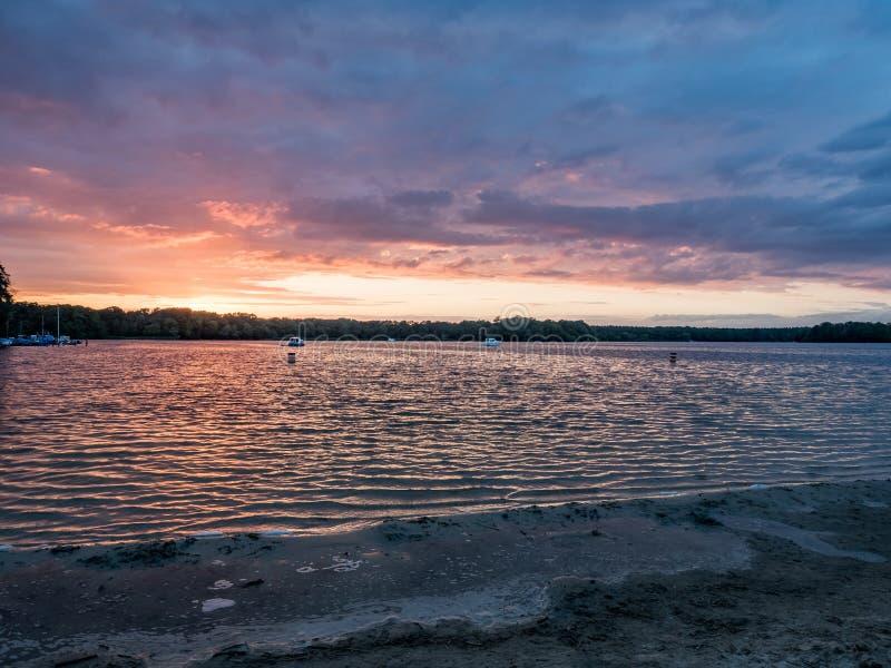 Słońce ustawia nad jeziorem w drewnach w lecie, zdjęcie stock
