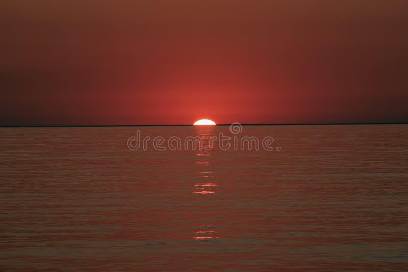 Słońce za morzem z falami i czerwony niebo przy zmierzchem zdjęcia royalty free