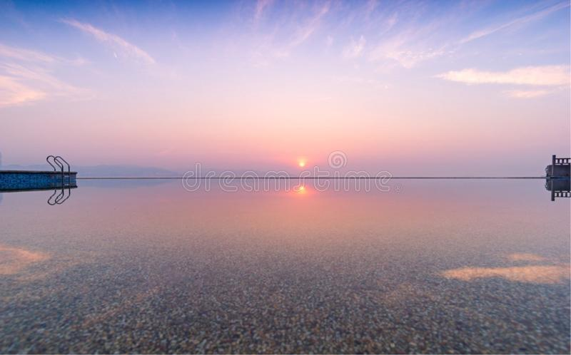 Słońce, zmierzch, zmierzch łuna, spokojna jezioro powierzchnia, biel chmurnieje i niebieskie niebo jest naprawdę cudowny obraz royalty free
