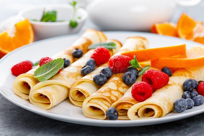 Słodcy bliny zawijający z świeżymi jagodami, krepami z czarną jagodą i malinką dla śniadania, fotografia stock