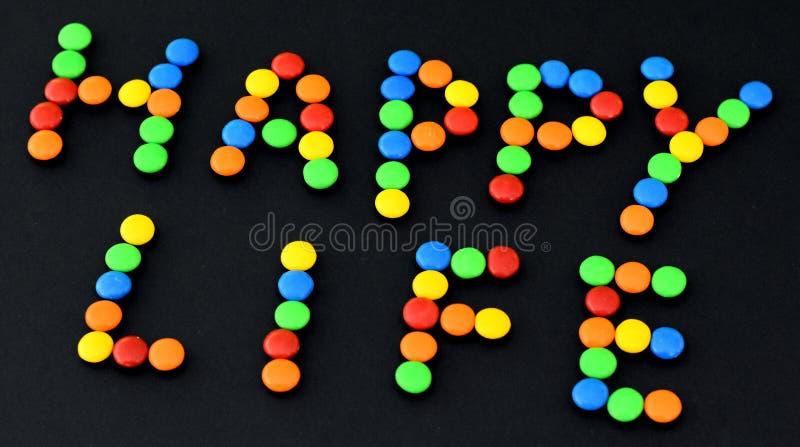 Słodcy bonbons z SZCZĘŚLIWYM życie tytułem zdjęcie stock