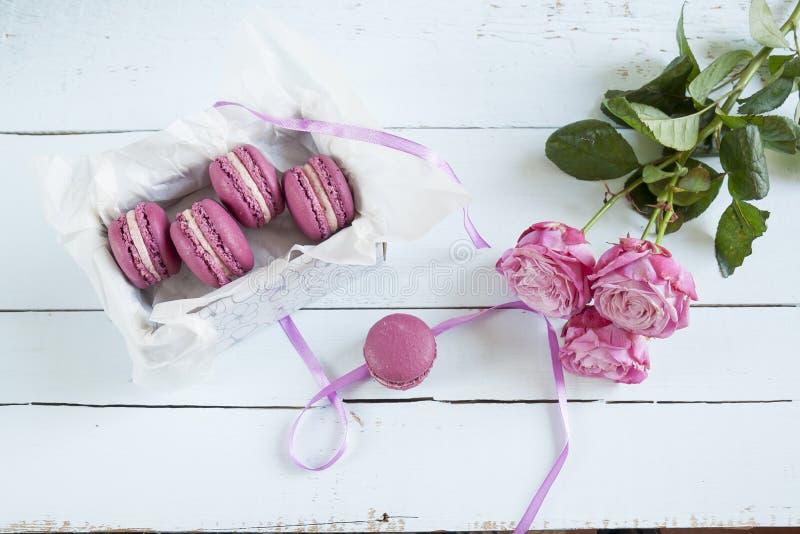 Słodcy ciemnopąsowi francuscy macaroons z pudełkiem i hiacyntem na świetle farbowali drewnianego tło zdjęcie royalty free