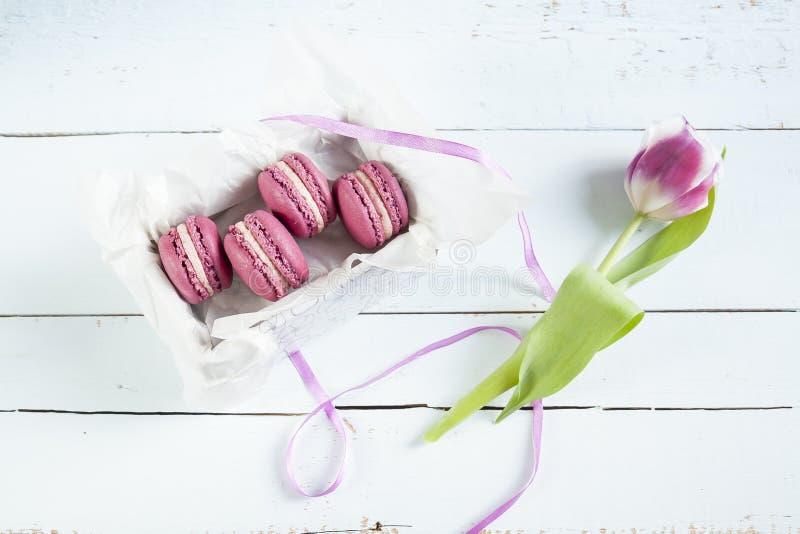 Słodcy ciemnopąsowi francuscy macaroons z pudełkiem i tulipanem na świetle farbowali drewnianego tło obrazy royalty free