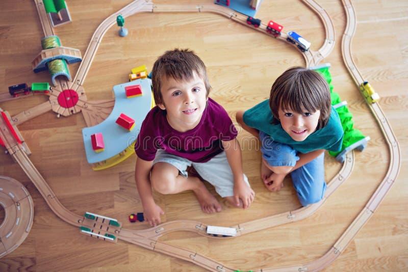Słodcy preschool dzieci, chłopiec bracia, bawić się z drewnianym poręczem zdjęcia stock
