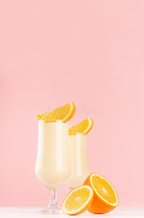 Słodcy rozochoceni milkshakes dekorowali plasterek owoc, pasiaste słoma na lekkim pastelowych menchii tle, pionowo zdjęcie stock