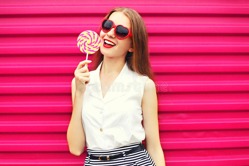Słodka ładna młoda kobieta z lizakiem nad menchiami fotografia stock