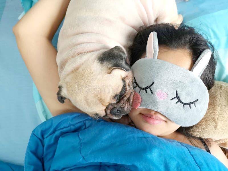 Słodka azjatykcia kobieta z maskowym i ślicznym szczeniaka mopsa psem śpi r obrazy stock