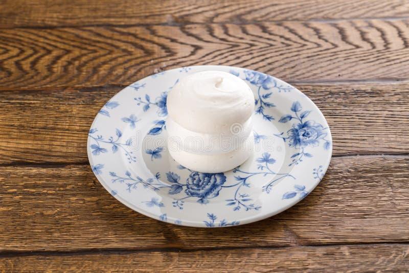 Słodka biała beza odizolowywająca na drewnianym tle fotografia stock